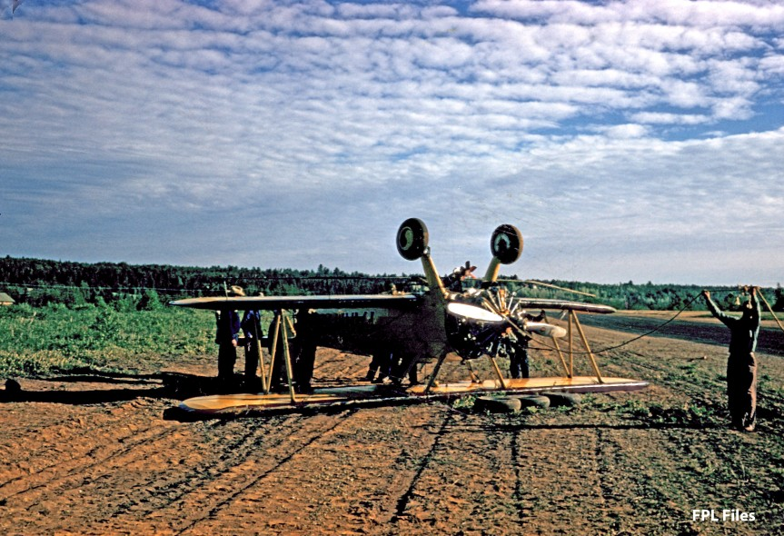 This is likely Farm-Air Stearman #124, N65806, upside down in a field. See story above. A lightening of the image revealed the Farm-Air logo on the fuselage. [FPL Files]
