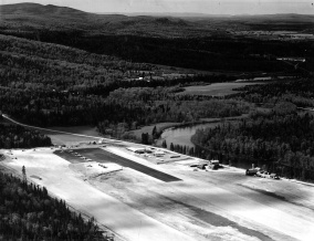 Aerial view of Nictau Airstrip looking south. Highway 385 and the Tobique River border the strip. Richard Arless Assoc., Nictau, NB, 27 May to 2 June, 1953.