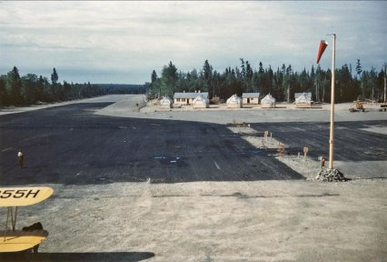 Camp buildings at Boston Brook airstrip, 1953, Mac McGlothin image. Taken from the control tower. Farm-Air N9955H is visible in the foreground. FPL files.