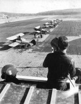 A line of Stearmans as seen from the control tower, Nictau Airstrip. Richard Arless Assoc., Nictau, NB, taken between 27 May and 2 June, 1953.